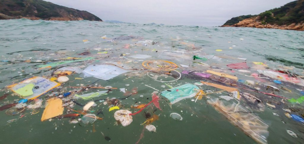 used masks and plastic floating in the ocean