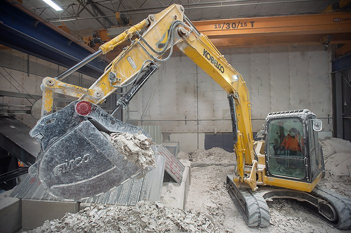 gypsum being fed into grinder to be recycled